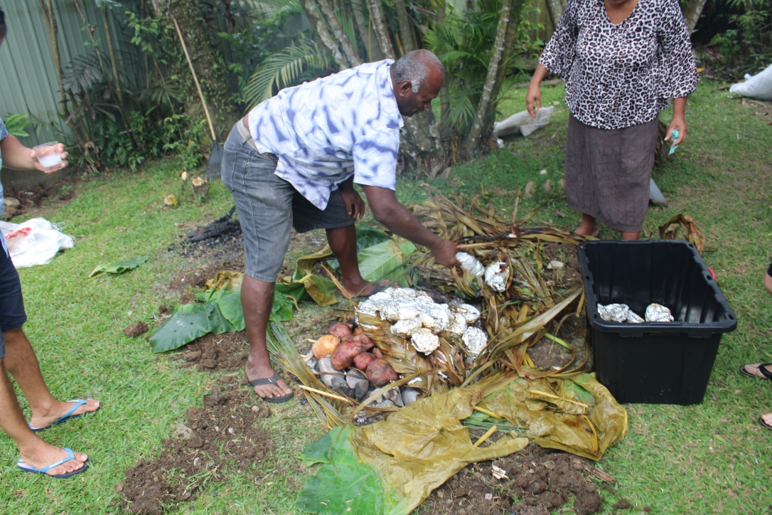 Removing cooked food from the lovo pit.